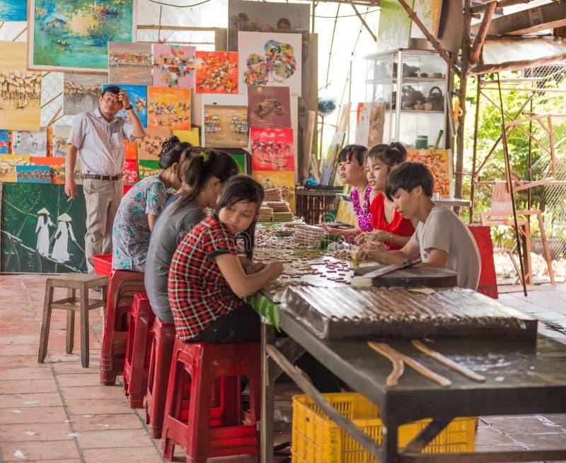 Unga arbetare i en vietnamesisk godisfabrik arkivfoton