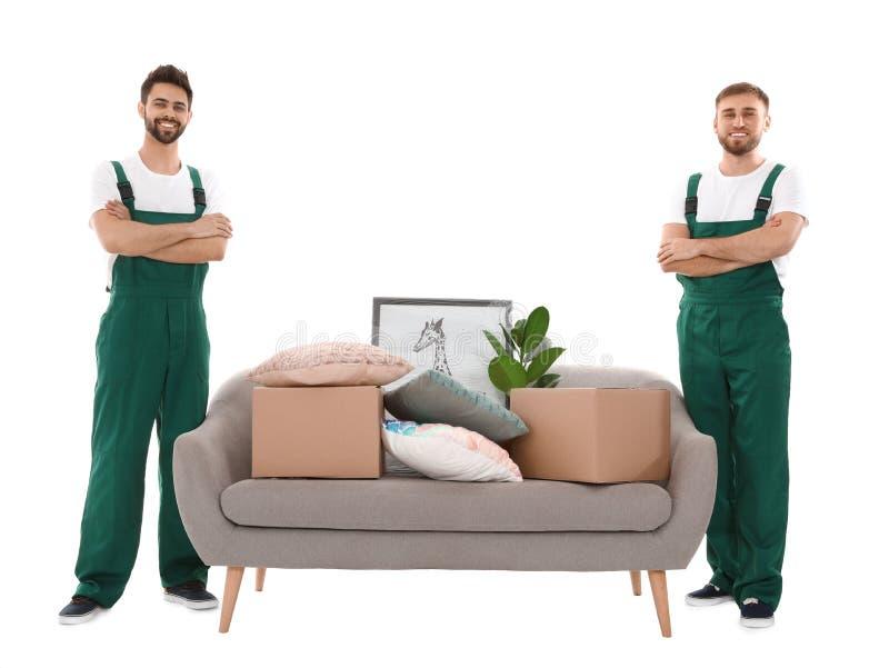 Unga arbetare nära soffan med material som isoleras på vit fotografering för bildbyråer