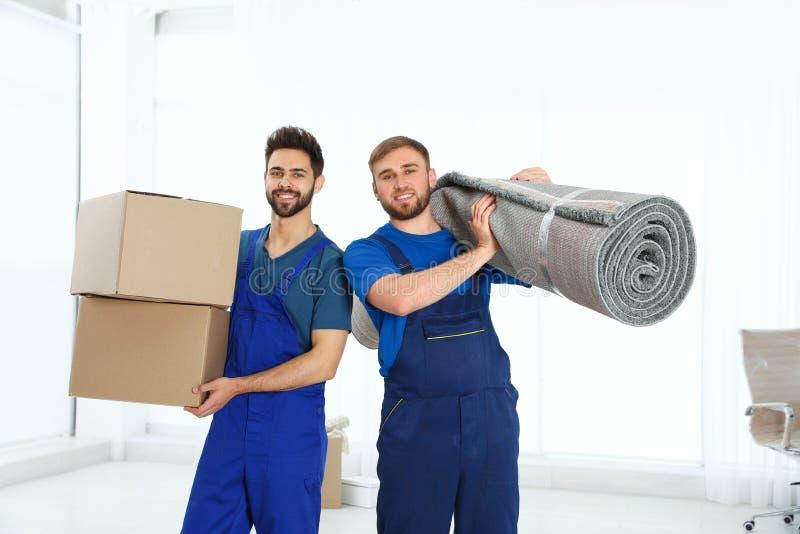Unga arbetare som bär rullande matta och askar i rum arkivbilder