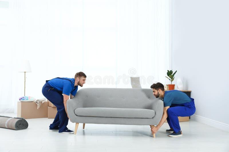 Unga arbetare som bär soffan i rum royaltyfri bild