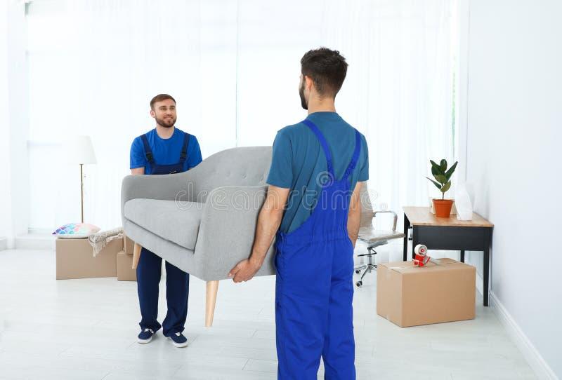 Unga arbetare som bär soffan i rum fotografering för bildbyråer