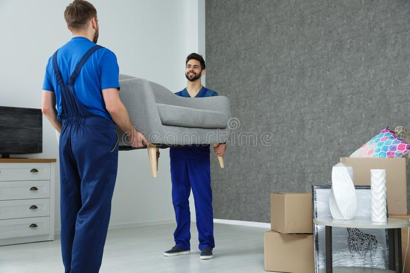 Unga arbetare som bär soffan i rum royaltyfria foton