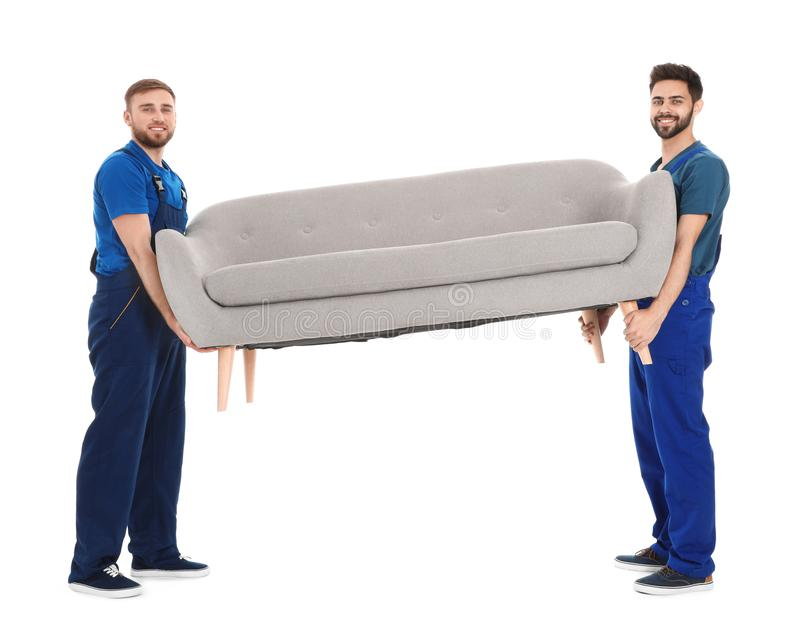Unga arbetare som bär soffan som isoleras på vit royaltyfri fotografi