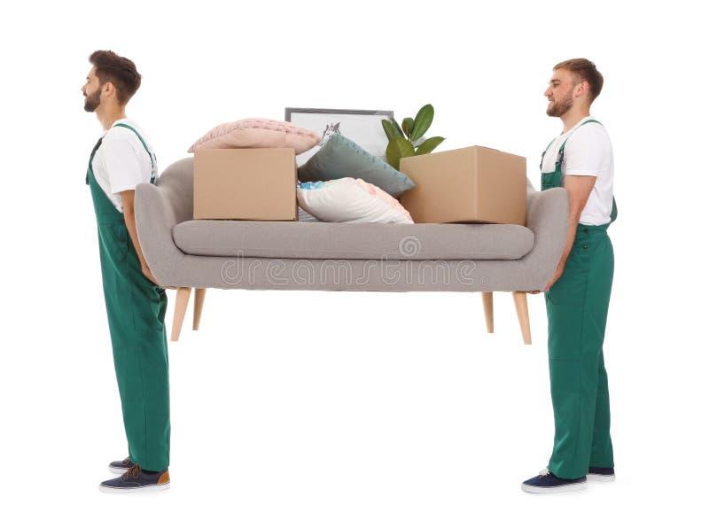Unga arbetare som bär soffan med material som isoleras på vit arkivbilder