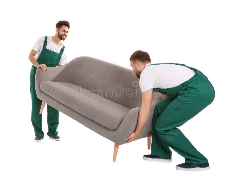 Unga arbetare som lyfter soffan som isoleras på vit arkivbilder