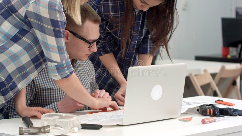 Unga arkitekter som kontrollerar teckningsmätningar med avdelaren fotografering för bildbyråer