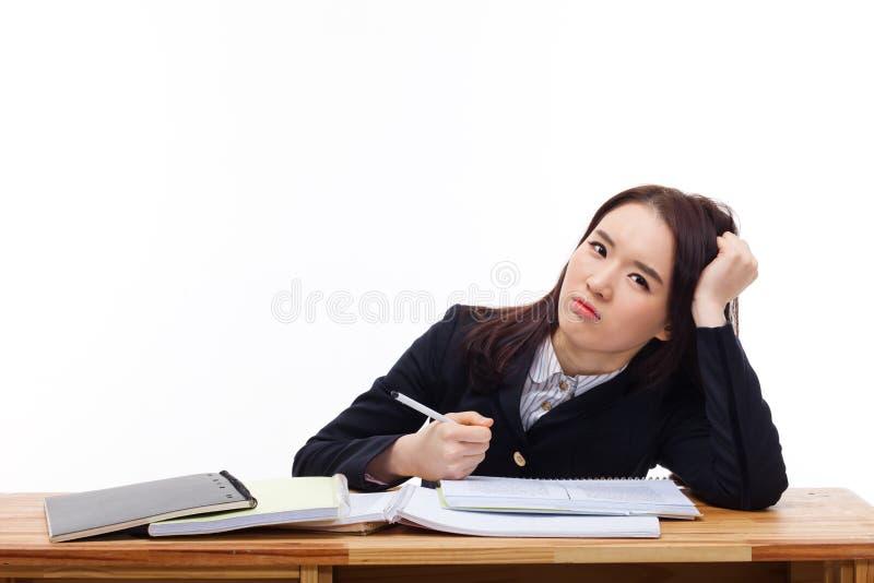 Unga asiatiska deltagaren som den har, besvärar på skrivbordet. royaltyfri fotografi