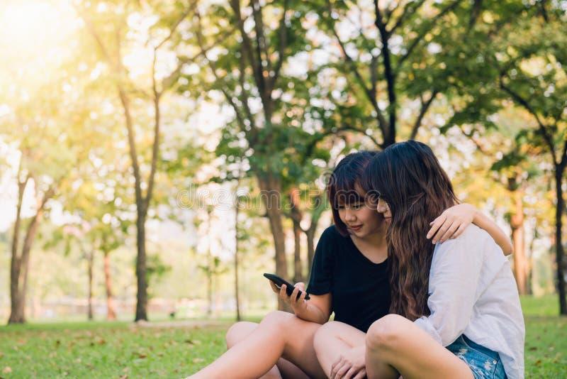 Unga asiatiska flickor för lycklig hipster som ler och ser smartphonen Livsstil- och kamratskapbegrepp arkivfoton