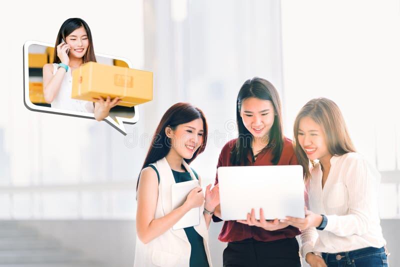Unga asiatiska kvinnor eller coworkers som använder bärbar datordatoren som direktanslutet tillsammans shoppar Företagsägareflick royaltyfri fotografi