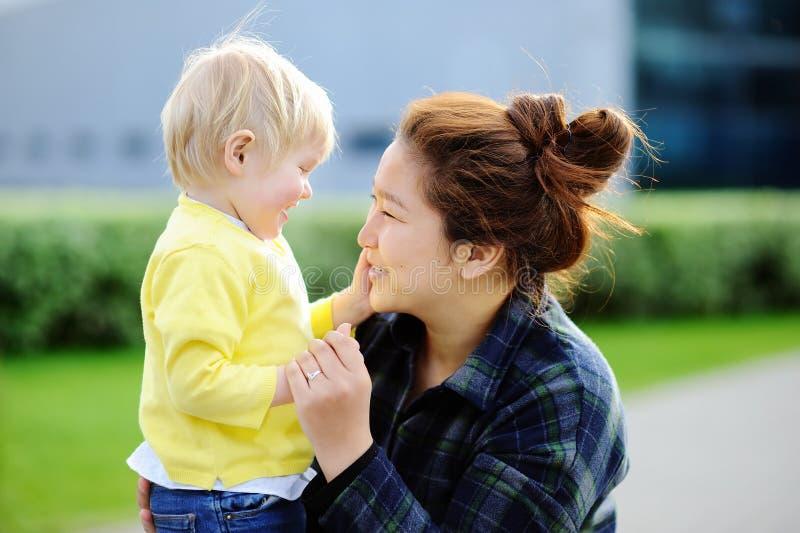 Unga asiatiska kvinnor med den gulliga caucasian litet barnpojken arkivfoton