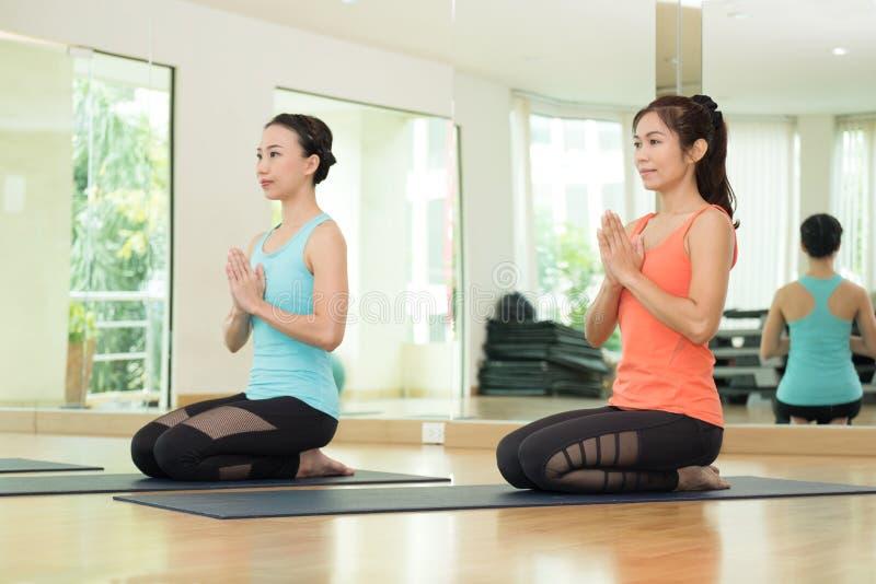 Unga asiatiska kvinnor som öva yoga, meditation i lotusblomma, poserar, heaen arkivfoto