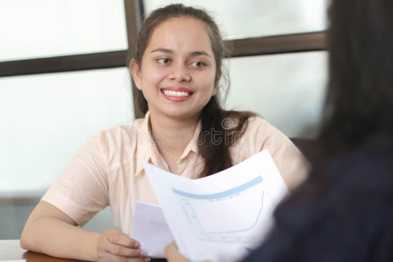 Unga asiatiska kvinnor som ler på arbetsintervjun, kvinnligt samtal med kvinnacoworkeren på kontoret royaltyfri bild