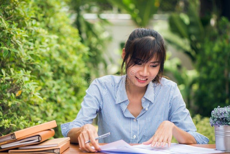 Unga asiatiska kvinnor som skriver läxa på skrivbordet i det fria, kvinna som arbetar med lyckligt sinnesrörelsebegrepp bilder fö arkivbild