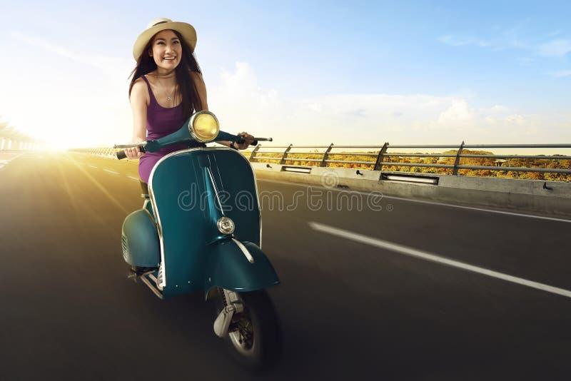 Unga asiatiska kvinnor tycker om att rida en sparkcykel och att ha gyckel royaltyfria foton