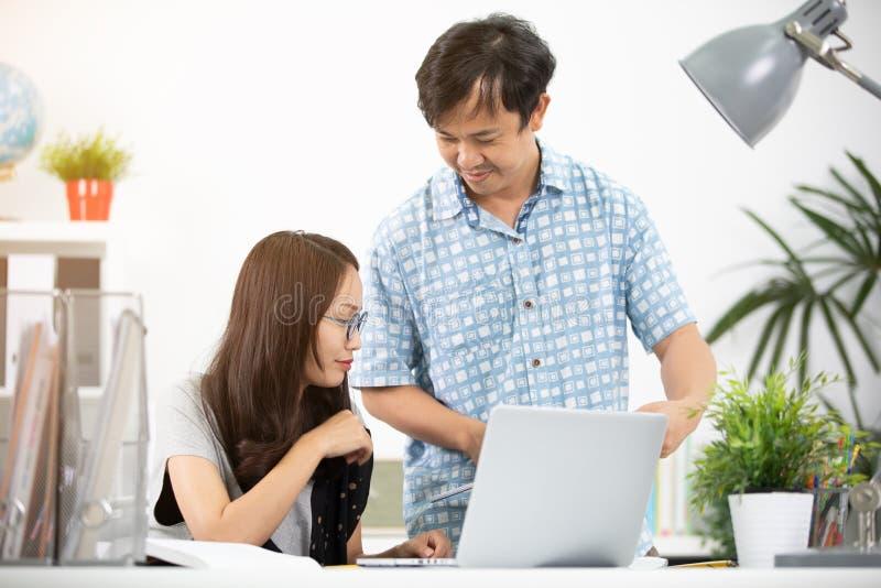 Unga asiatiska lyckliga ledare, anställda som diskuterar nytt projekt arkivbilder