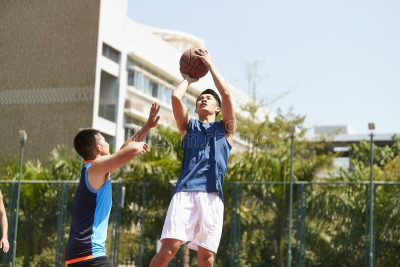 Unga asiatiska män som spelar basket arkivfoto
