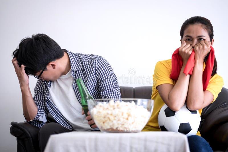 Unga asiatiska par älskar den hållande ögonen på fotbollsmatchen på tv och att hurra royaltyfria bilder