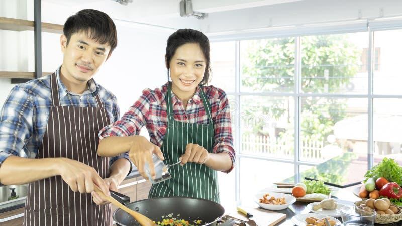 Unga asiatiska par är lyckliga att laga mat tillsammans på ferie royaltyfri fotografi