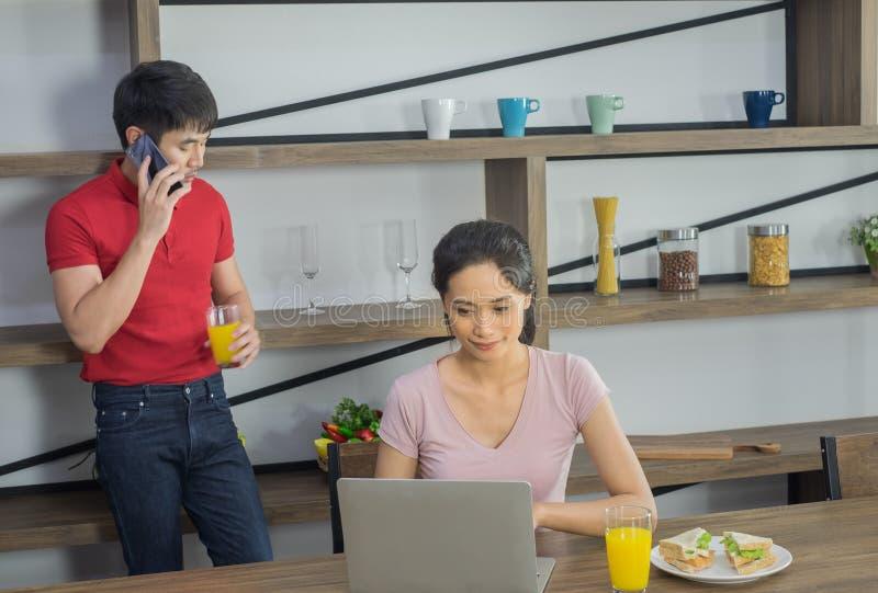 Unga asiatiska par, att fokusera av till kvinnan ser datorbärbara datorn royaltyfri foto