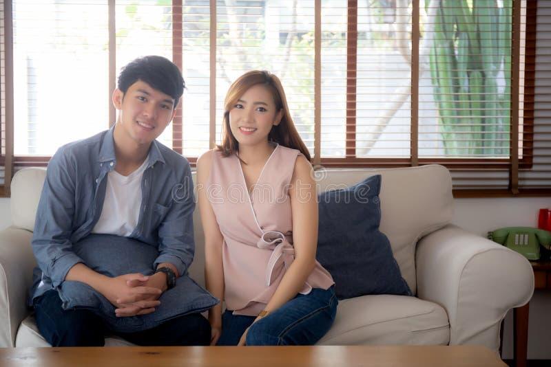 Unga asiatiska par för härlig stående att koppla av och tillfredsställt tillsammans i hemmastadd vardagsrum, sittande soffa för f arkivfoton