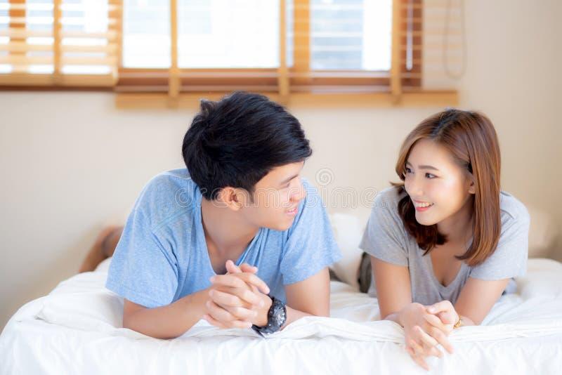 Unga asiatiska par för härlig stående att koppla av och tillfredsställt tillsammans i sovrum hemma, familj som sitter på säng royaltyfri foto