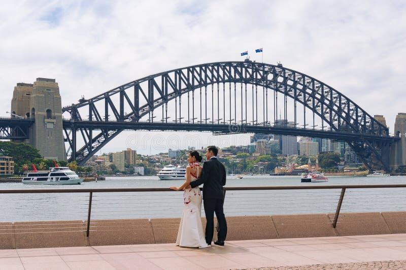 Unga asiatiska par som poserar mot Sydney Harbour Bridge på backg arkivfoto