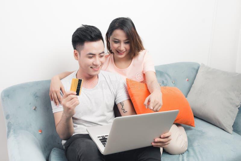 Unga asiatiska par som surfar på internet och shoppar med bärbara datorn Modern vit lägenhet i bakgrund royaltyfria foton