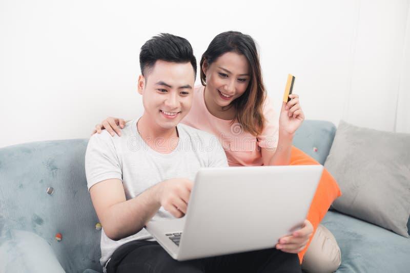 Unga asiatiska par som surfar på internet och shoppar med bärbara datorn Modern vit lägenhet i bakgrund royaltyfri bild