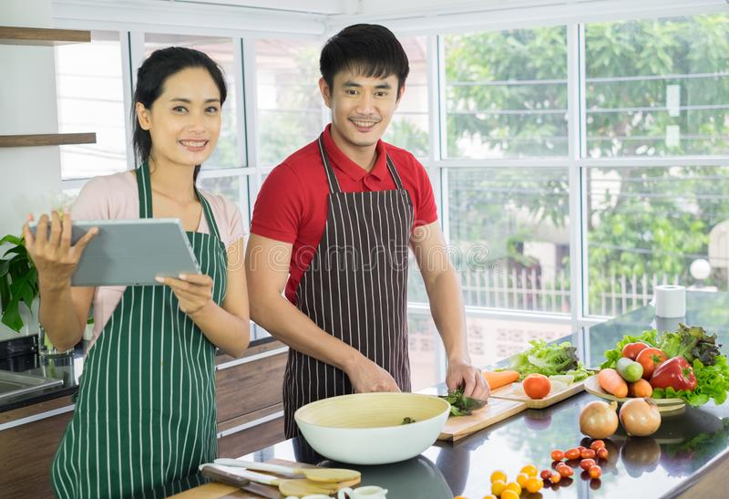 Unga asiatiska par Stående leende som lagar mat i köket förbered sallad för mat tillsammans lyckligt royaltyfri fotografi