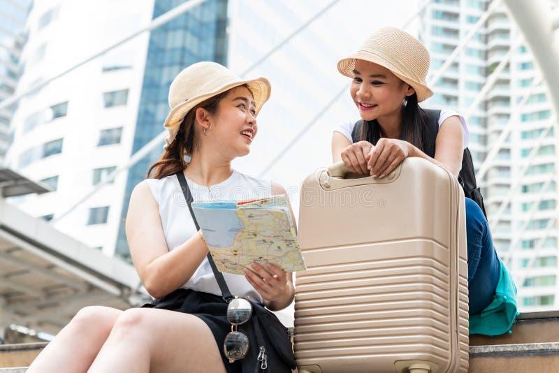 Unga asiatiska turist- kvinnor som bär hattar som söker efter riktning från en översikt med att le framsidor arkivbilder