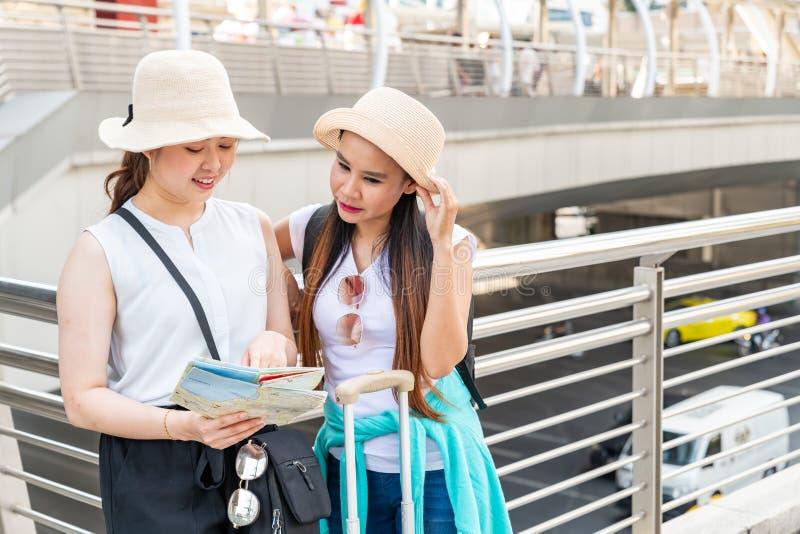 Unga asiatiska turist- kvinnor som bär hattar som söker efter riktning från en översikt med att le framsidor royaltyfri fotografi
