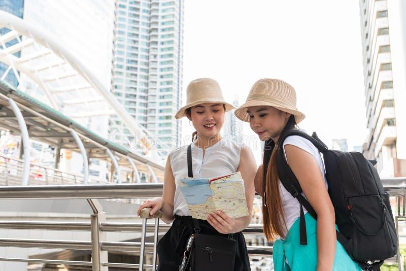 Unga asiatiska turist- kvinnor som bär hattar som söker efter riktning från en översikt med att le framsidor arkivfoton