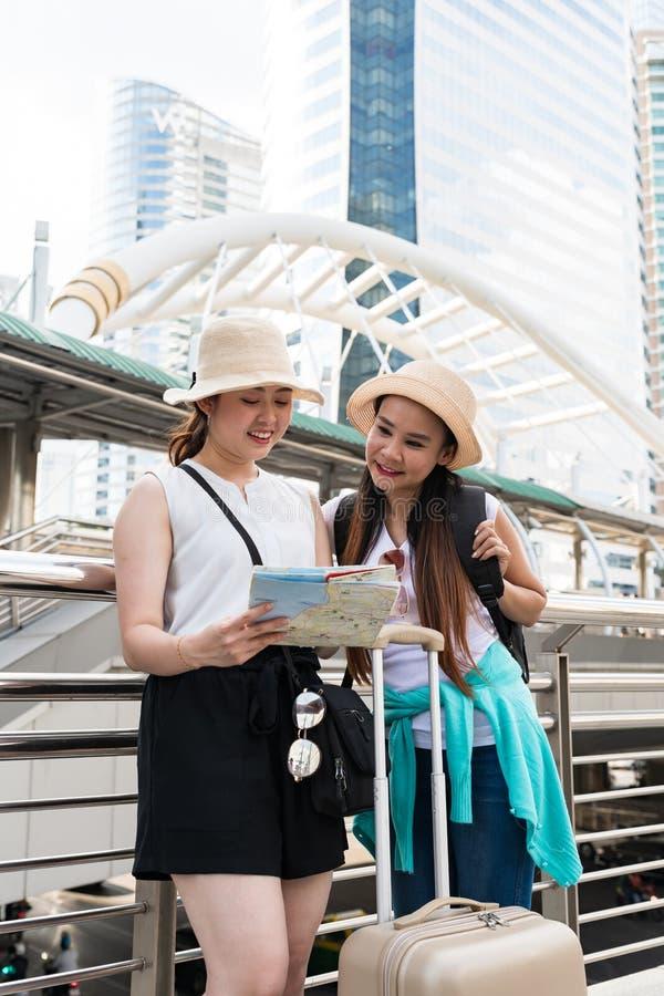 Unga asiatiska turist- kvinnor som bär hattar som söker efter riktning från en översikt med att le framsidor royaltyfri foto