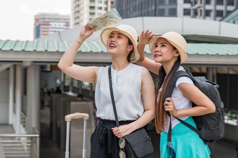 Unga asiatiska turist- kvinnor som ser in i avstånd och rymmer händer på pannor royaltyfri fotografi