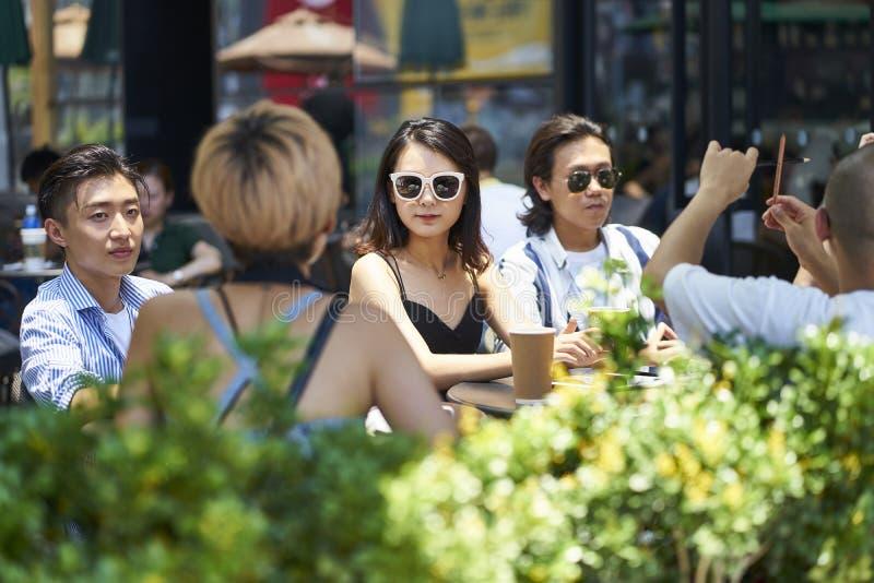Unga asiatiska vuxna m?nniskor som kopplar av i coffee shop royaltyfri foto