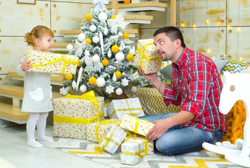 Unga askar för gåva för fader- och litet barndotter undersökande nära den dekorerade julgranen hemma royaltyfria bilder