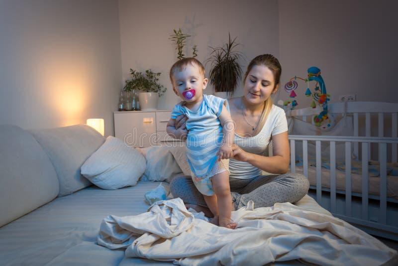 Unga att bry sig ändrande blöjor för moder till hennes sömnigt behandla som ett barn pojken, innan de går att sova fotografering för bildbyråer