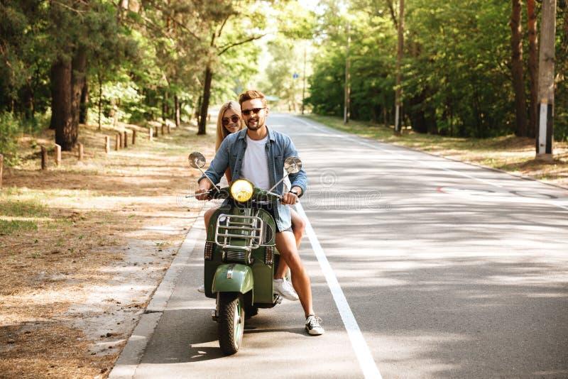Unga attraktiva älska par på sparkcykeln utomhus åt sidan se royaltyfri fotografi