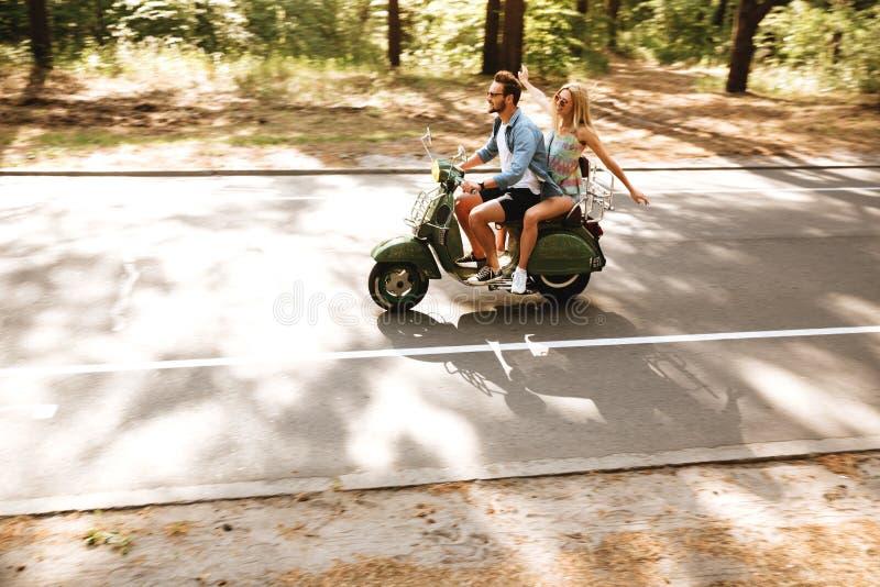 Unga attraktiva älska par på sparkcykeln utomhus åt sidan se arkivbilder