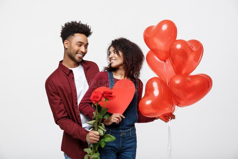 Unga attraktiva afrikansk amerikanpar på datummärkning med den röda rosen, hjärta och ballongen royaltyfria foton