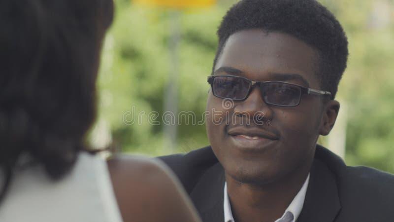 Unga attraktiva afro--amerikan affärspar som talar och ler, medan sitta i kafé arkivfoton