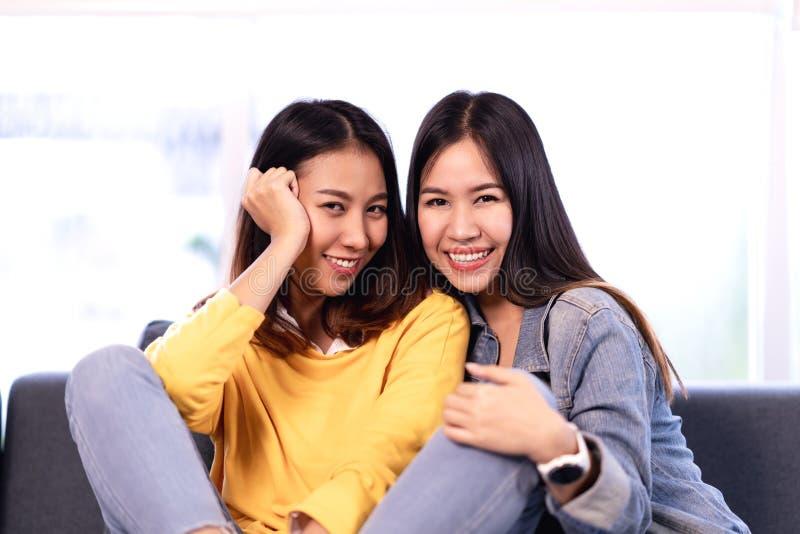 Unga attraktiva asiatiska flickvänner som tillsammans sitter på le för soffasoffa den hemmastadda och seende kameran arkivbild