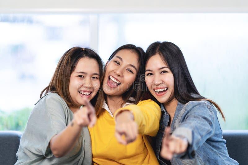 Unga attraktiva asiatiska kvinnor eller tre bästa vän som sitter och pekar dig som ser kameran arkivbilder
