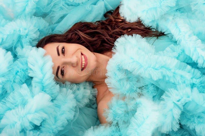 Unga attraktiva brunettkvinnalögner som slås in i ett fluffigt moln av hennes blåa klänning royaltyfri fotografi