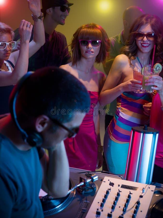 Unga attraktiva flickor som dansar på partit med dj royaltyfri foto
