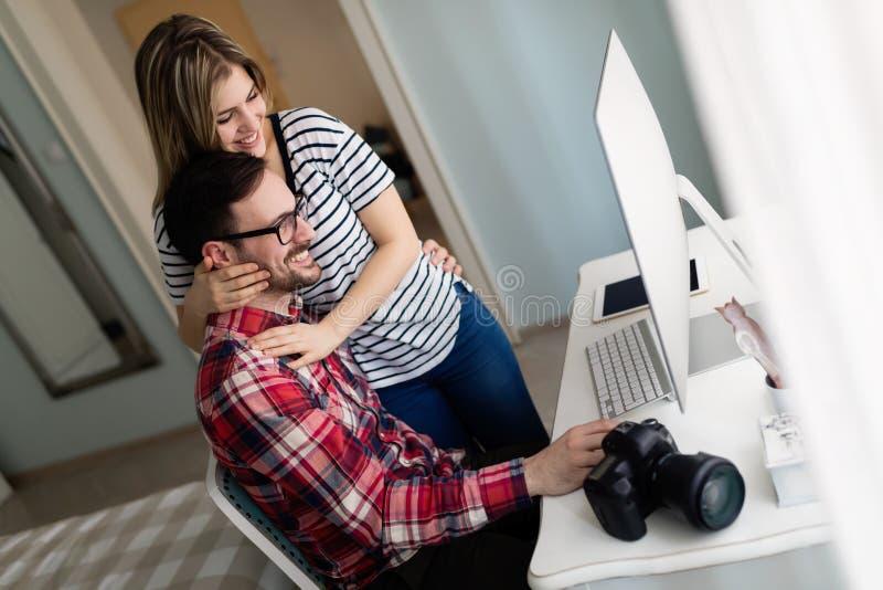 Unga attraktiva formgivare som tillsammans hemifrån arbetar arkivfoto