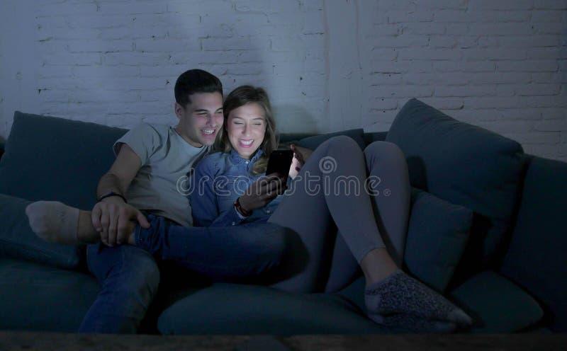 Unga attraktiva och lyckliga par genom att använda internet app på mobiltelefonen som tycker om och skrattar sittande tillsammans fotografering för bildbyråer