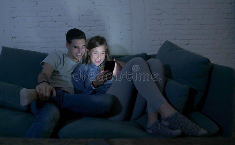 Unga attraktiva och lyckliga par genom att använda internet app på mobiltelefonen som tycker om och skrattar sittande tillsammans arkivbild