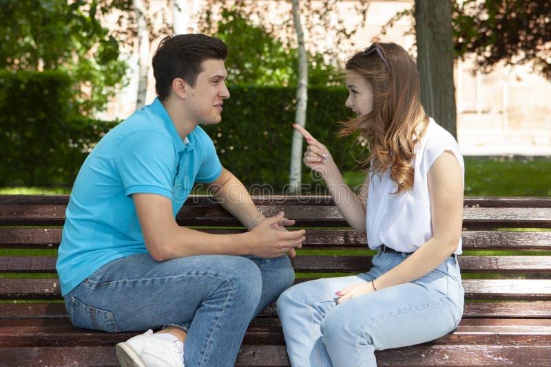 Unga attraktiva par har ett argument över något, utomhus- fors arkivbilder