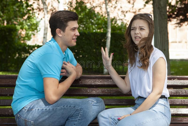 Unga attraktiva par har ett argument över något, utomhus- fors royaltyfri bild